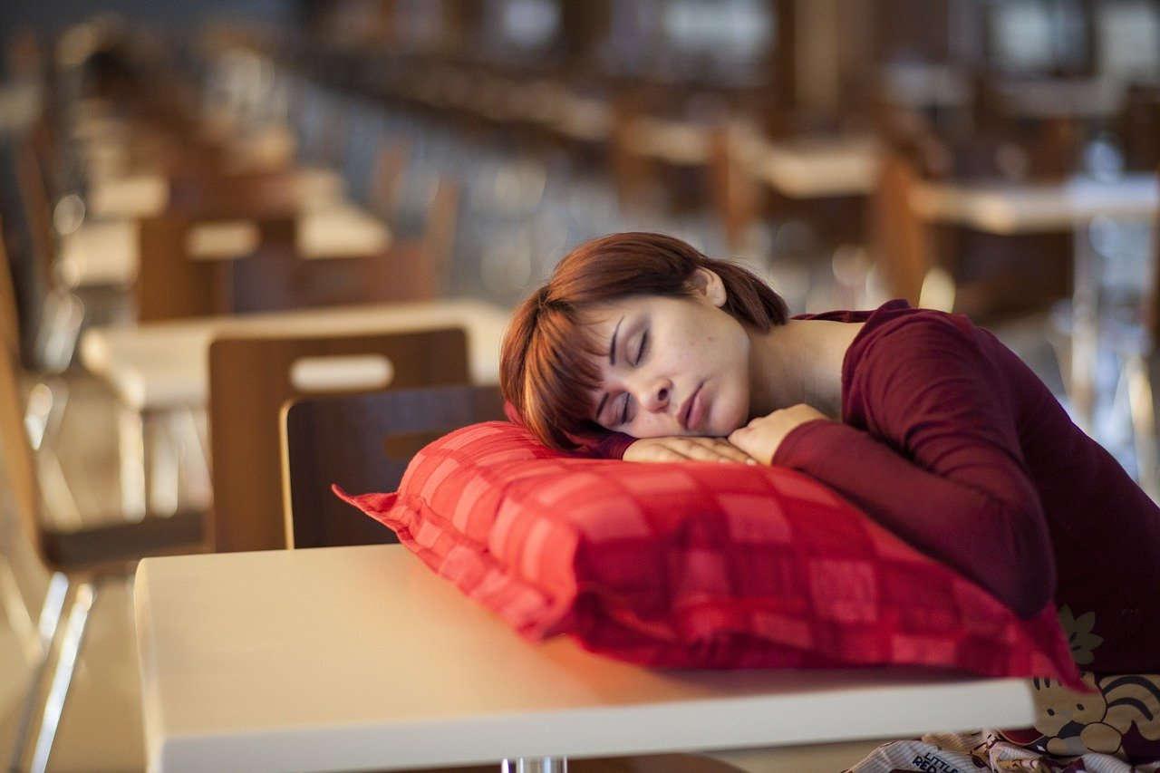 בחורה ישנה על כרית שמונחת על שולחן