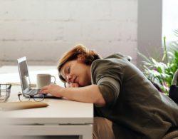 אשה ישנה על שולחן העבודה