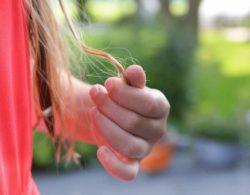 בחורה אוחזת בקצוות שיער