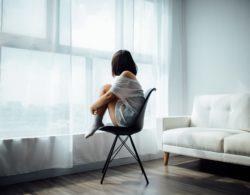 אישה יושבת על כסא וצופה בחלון מבעד לוילון
