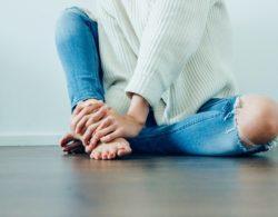 אישה אוחזת בכפות רגליה