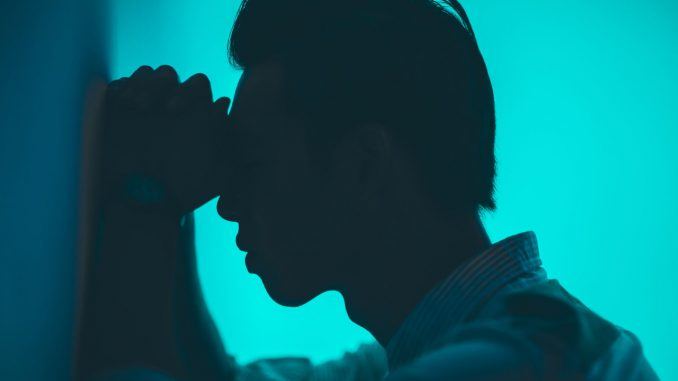 פרופיל של גבר הנשען על הקיר בכאב
