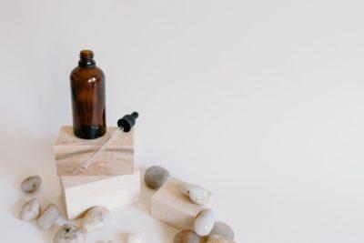בקבוקון חום לצד מזלף מונח על קוביות עץ ליד חלוקי נחל